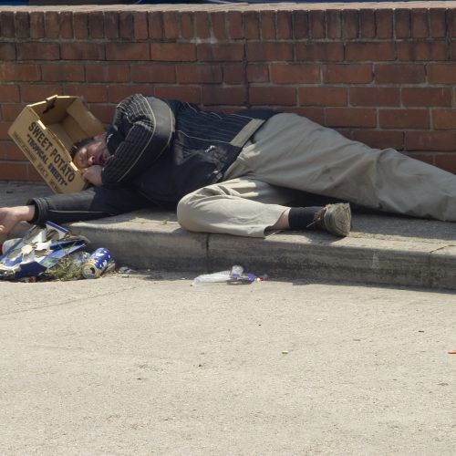 Man lying on street with sweet potato box